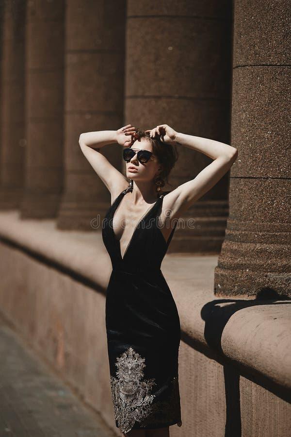 Belle, à la mode fille de brune dans la robe noire et lunettes de soleil posant dehors, ressort photo libre de droits