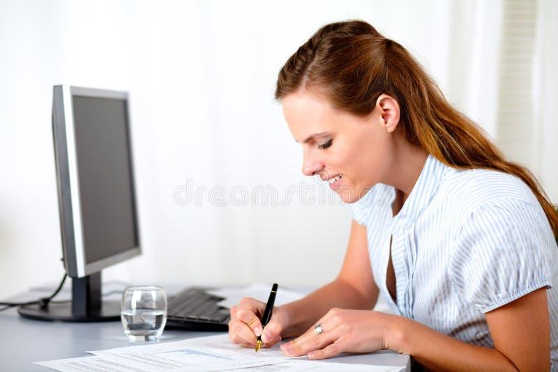 Belle écriture blonde de dame sur le lieu de travail images libres de droits
