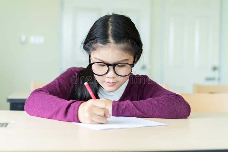 Belle écriture de fille sur un papier blanc dans la salle de classe photographie stock libre de droits