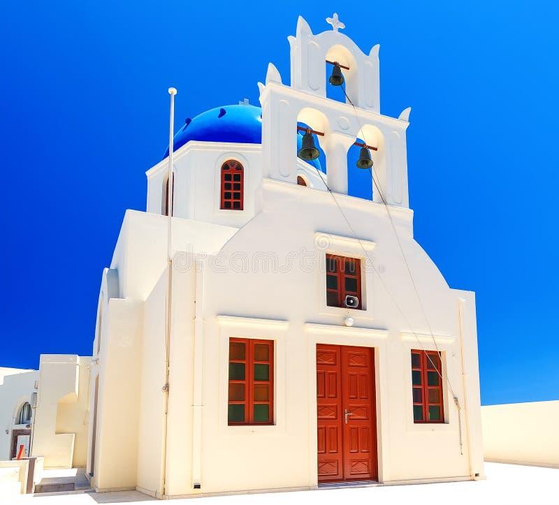 Belle église blanche orthodoxe grecque avec une tour de cloche contre le ciel bleu clair dans le village d'Oia sur Santorini photos libres de droits