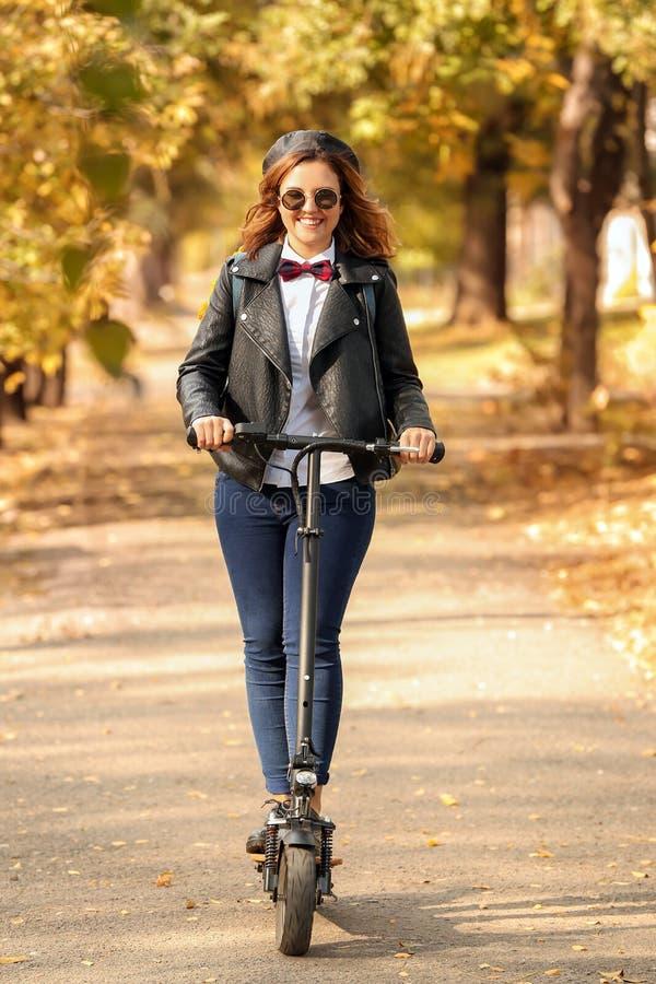 Belle équitation de jeune femme sur le scooter en parc d'automne images stock