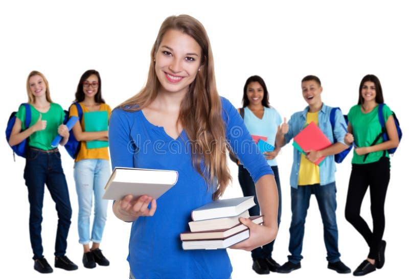 Belle étudiante allemande avec des livres et groupe d'étudiants photographie stock libre de droits
