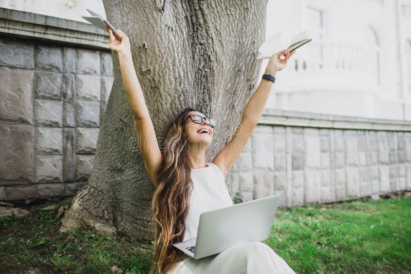 Belle étudiante apprenant ses leçons se reposant sur l'herbe photographie stock