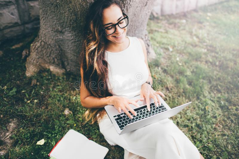 Belle étudiante apprenant ses leçons se reposant sur l'herbe photo libre de droits