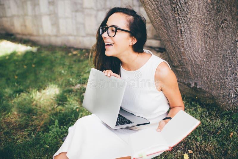 Belle étudiante apprenant ses leçons se reposant sur l'herbe photo stock