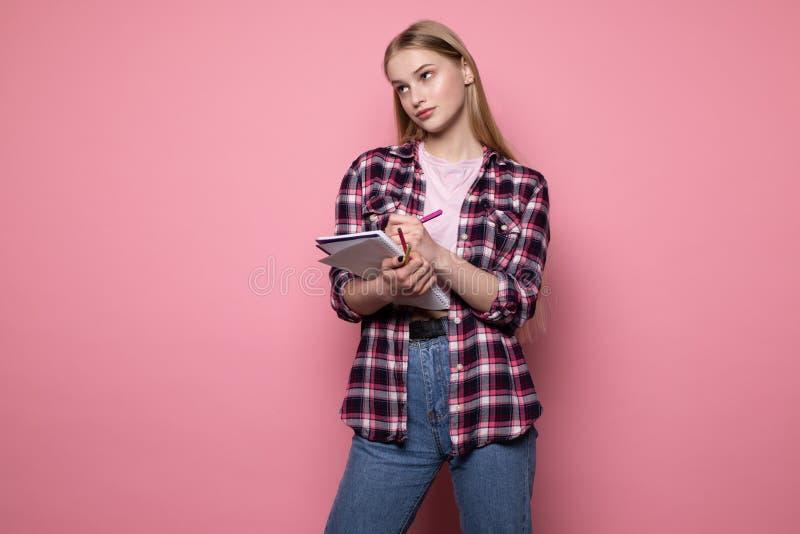 Belle ?tudiante blonde boulevers?e dans des v?tements sport se tenant contre le mur rose images libres de droits