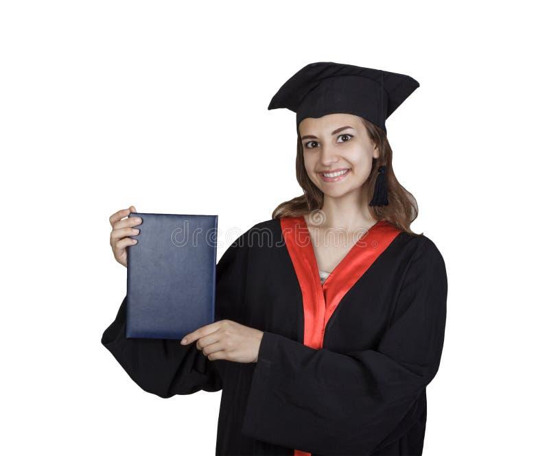 Belle étudiante licenciée dans le manteau montrant le panneau vide de plaquette, d'isolement sur le fond blanc photo stock