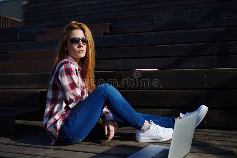 Belle étudiante se préparant aux conférences tout en employant son filet-livre sur le campus photographie stock libre de droits