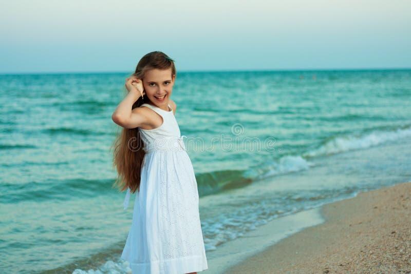 Belle adolescente avec la coquille sur la plage de soirée photo stock