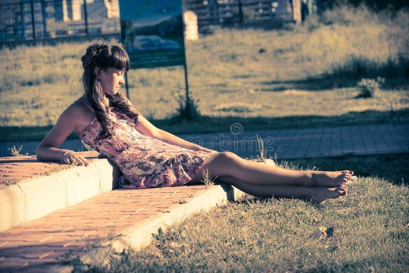 Belle adolescente dans la robe rose avec de longs cheveux en parc vert d'été photo stock