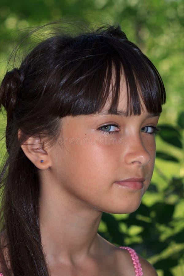 Belle adolescente dans la robe rose avec de longs cheveux en parc vert d'été image libre de droits