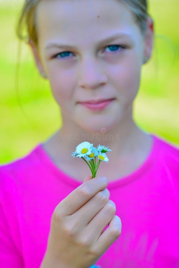 Belle adolescente de sourire avec le petit bouquet des marguerites image libre de droits