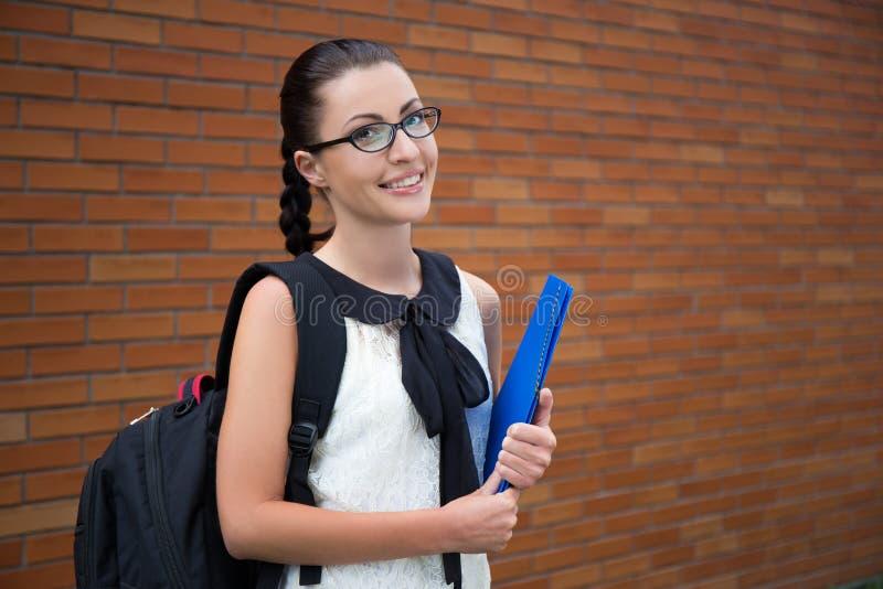 Belle adolescente de sourire avec le sac à dos images stock