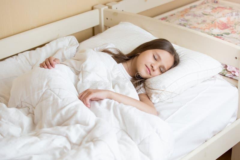 Belle adolescente dormant sur la toile blanche photo stock