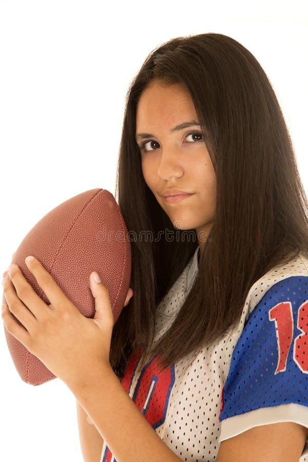 Belle adolescente hispanique tenant un football américain photo stock