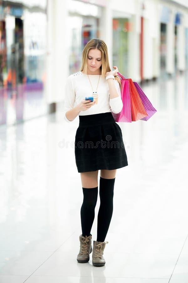 Belle adolescente regardant le téléphone portable dans le cente d'achats photos stock