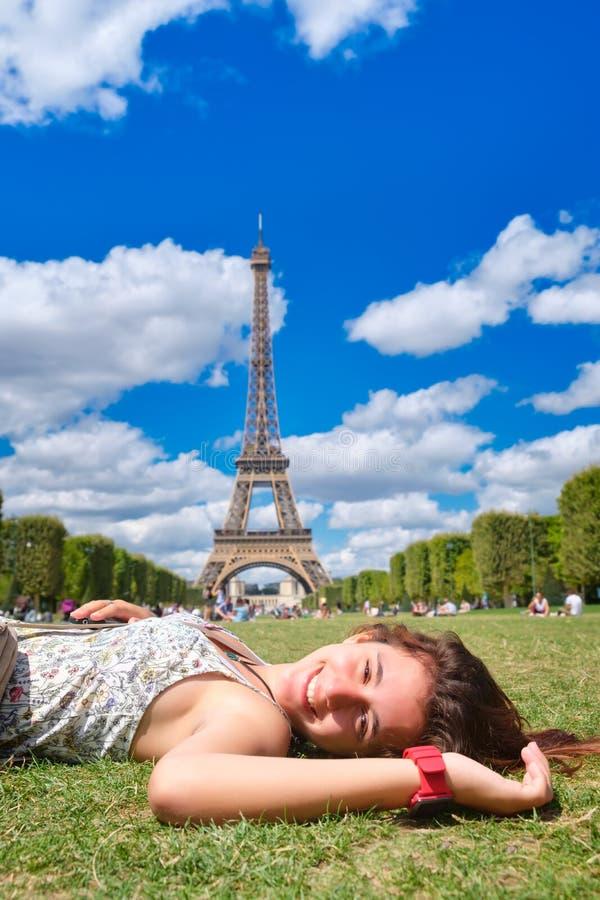 Belle adolescente s'étendant sur l'herbe à Paris près de Tour Eiffel images stock