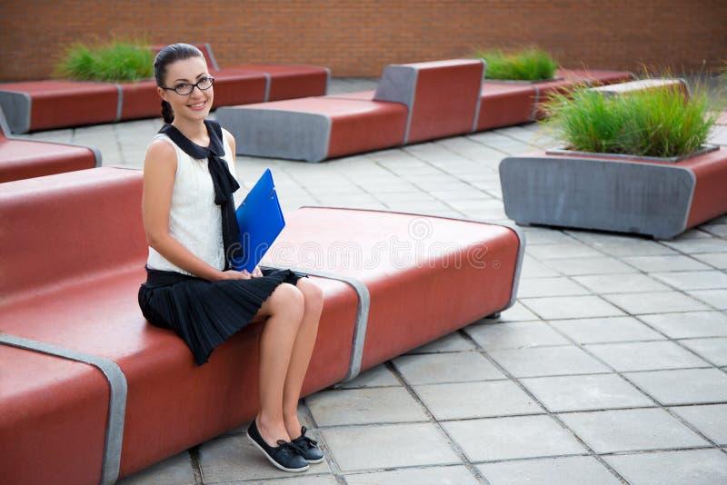 Belle adolescente s'asseyant sur le banc image libre de droits