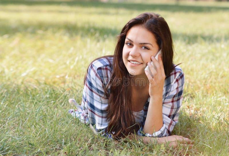 Belle adolescente se trouvant sur le champ de l'herbe verte et de l'entretien par le téléphone photos stock