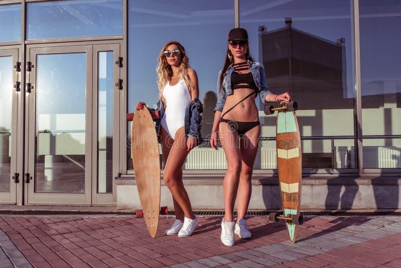 Belle amiche delle ragazze, due donne che posano pattino, longboard, costruzione di vetro di finestra del fondo Il concetto fotografia stock