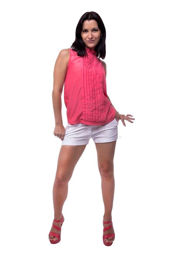Belle, attirante jeune femme dans le chemisier et shorts courts souriant par espièglerie, posant, regard malfaisant, intégral image libre de droits