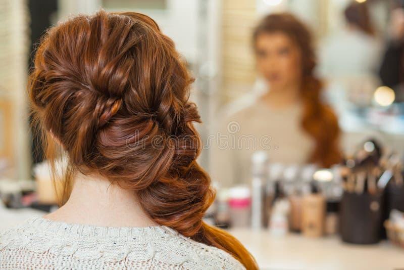 Belle, avec longtemps, la fille velue rousse, coiffeuse tisse une tresse française, dans un salon de beauté images stock