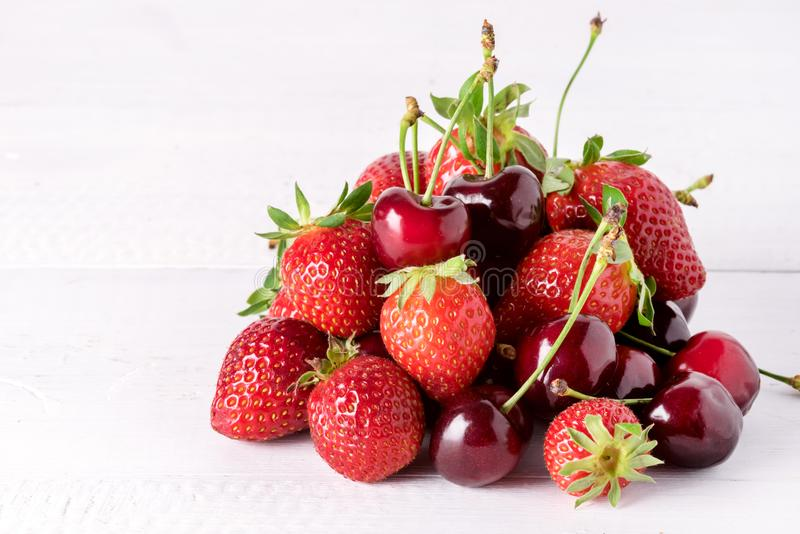 Belle bacche mature fresche sulle fragole dolci e su Cherry Copy Space di un fondo di legno bianco immagini stock