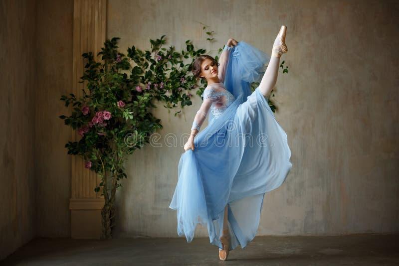 Belle ballerine gracieuse de fille dans la danse bleue de robe au point photographie stock