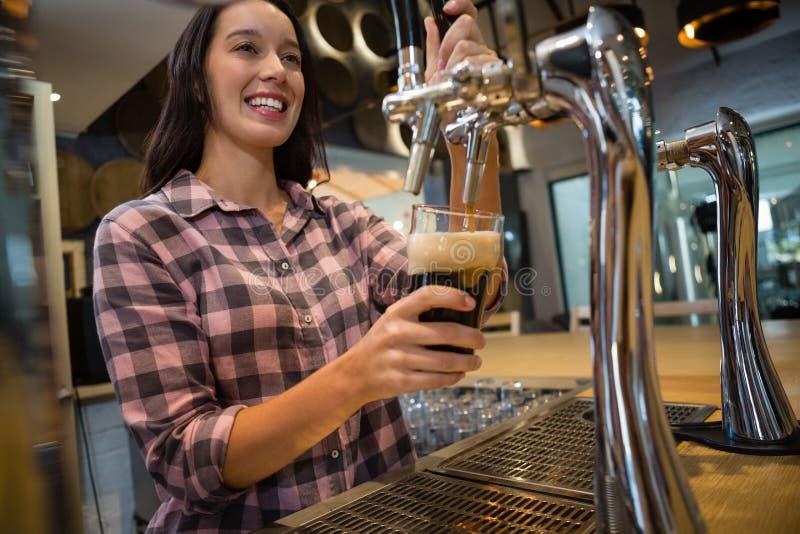 Belle barmaid préparant la boisson à la barre image libre de droits