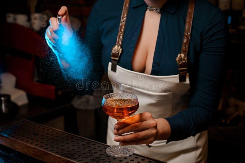 Belle barmaid sexy pulvérisant amer de couleur bleue sur le verre photos libres de droits