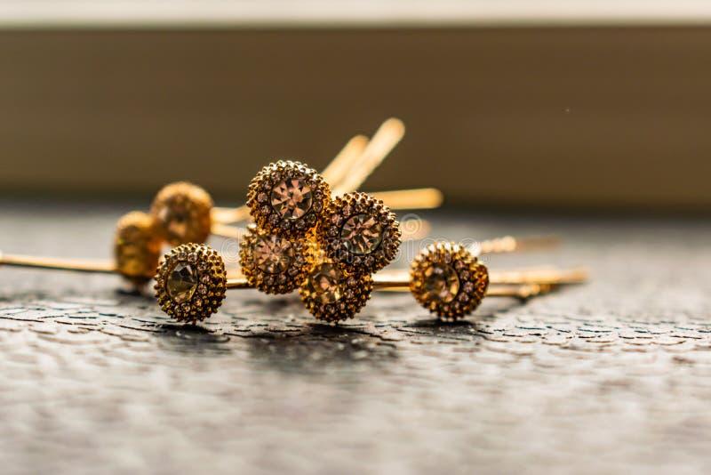 Belle barrette automatique avec les pierres brillantes et les perles roses sur le fond texturisé foncé Épingles à cheveux d'or av photographie stock libre de droits