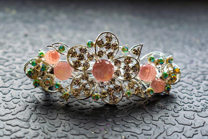 Belle barrette automatique avec les pierres brillantes et les perles roses sur le fond texturisé foncé Épingles à cheveux d'or av image stock