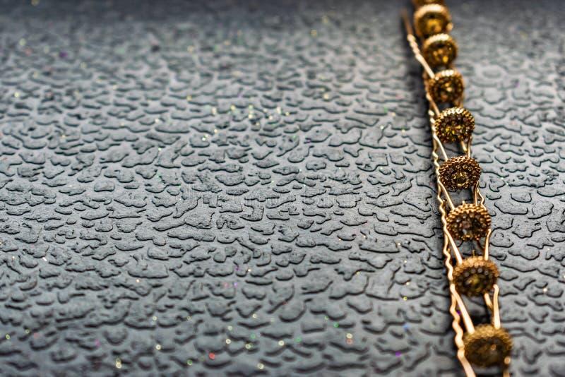 Belle barrette automatique avec les pierres brillantes et les perles roses sur le fond texturisé foncé Épingles à cheveux d'or av photos stock