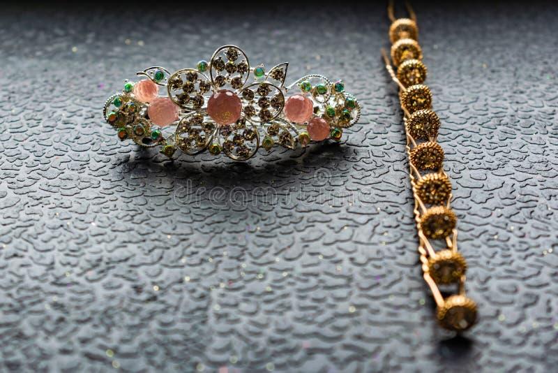 Belle barrette automatique avec les pierres brillantes et les perles roses sur le fond texturisé foncé Épingles à cheveux d'or av photo stock