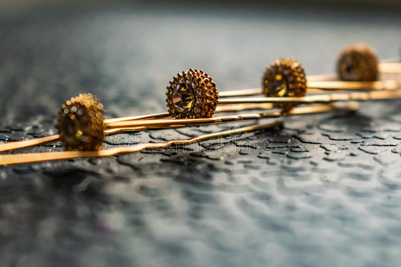 Belle barrette automatique avec les pierres brillantes et les perles roses sur le fond texturisé foncé Épingles à cheveux d'or av images stock