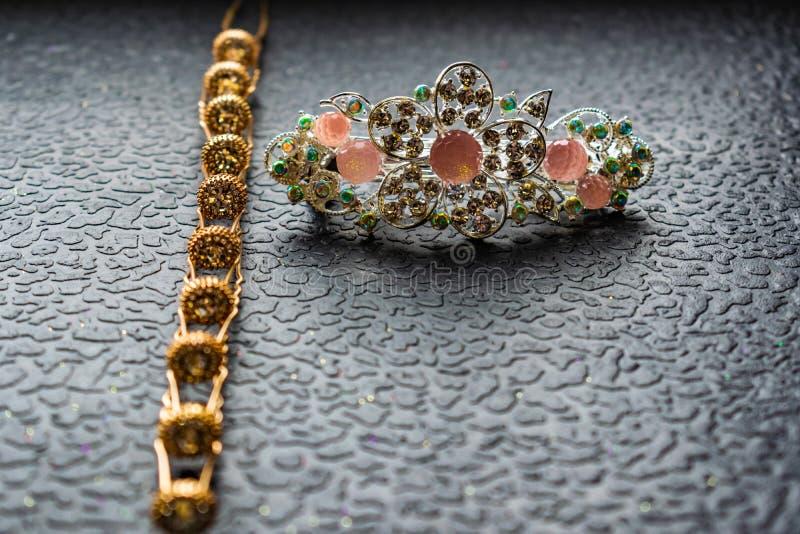Belle barrette automatique avec les pierres brillantes et les perles roses sur le fond texturisé foncé Épingles à cheveux d'or av image libre de droits