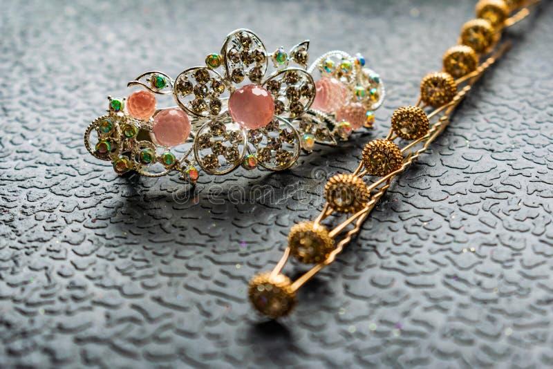 Belle barrette automatique avec les pierres brillantes et les perles roses sur le fond texturisé foncé Épingles à cheveux d'or av photographie stock