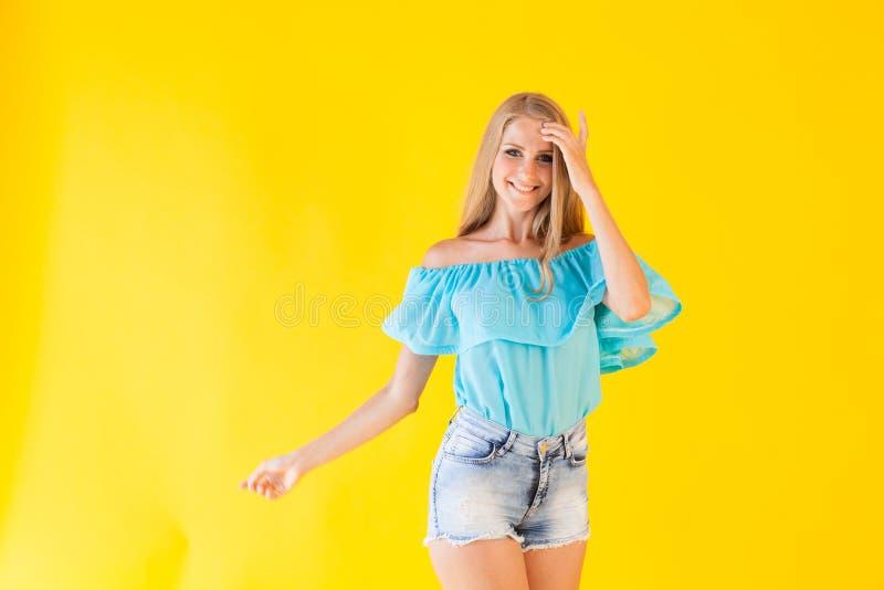 Belle blonde avec des yeux bleus posant sur un fond jaune photographie stock libre de droits