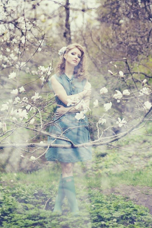 Download Belle Blonde Avec La Belle Coiffure Dans La Robe Bleue De Vintage Dans Une Magnolia Luxuriante De Jardin De Ressort Image stock - Image du coupe, femelle: 87709121
