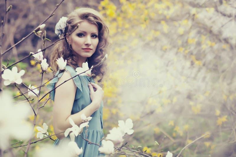 Download Belle Blonde Avec La Belle Coiffure Dans La Robe Bleue De Vintage Dans Une Magnolia Luxuriante De Jardin De Ressort Photo stock - Image du cher, lumineux: 87709126