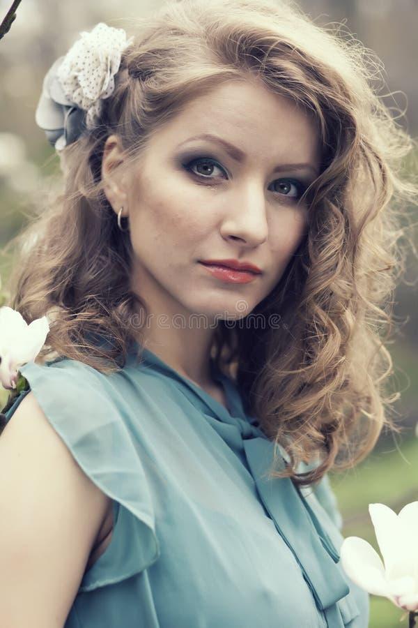 Download Belle Blonde Avec La Belle Coiffure Dans La Robe Bleue De Vintage Dans Une Magnolia Luxuriante De Jardin De Ressort Photo stock - Image du ange, soirée: 87709174