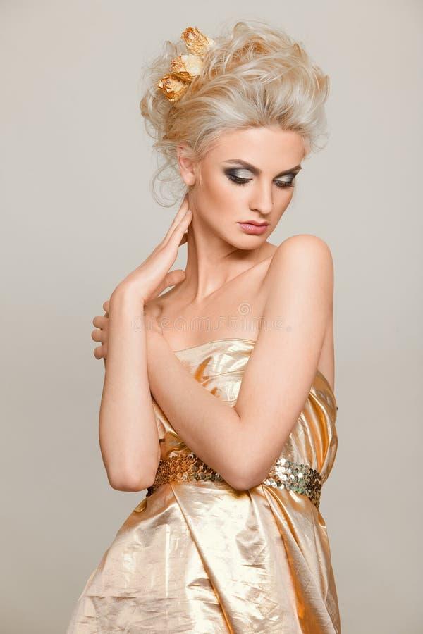 Belle blonde dans la robe d'or photos stock