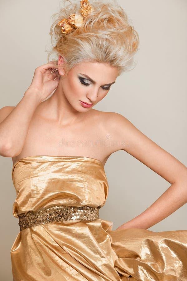 Belle blonde dans la robe d'or images stock
