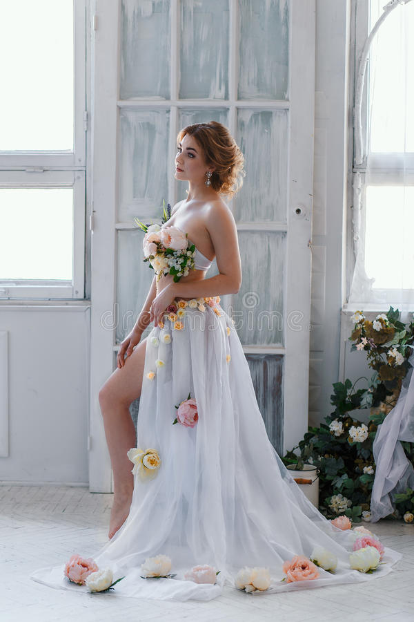 Belle blonde dans la robe des fleurs photo libre de droits