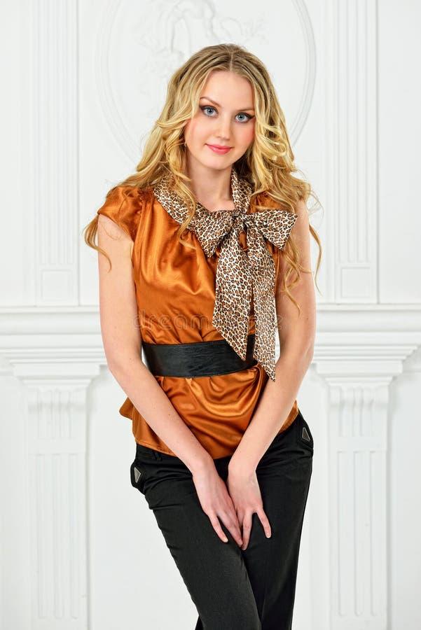 Belle blonde dans le chemisier de couleur de moutarde. photos libres de droits