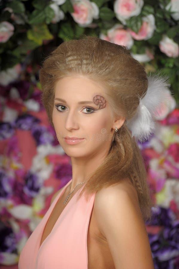 Belle blonde dans une robe rose dans le jardin photographie stock