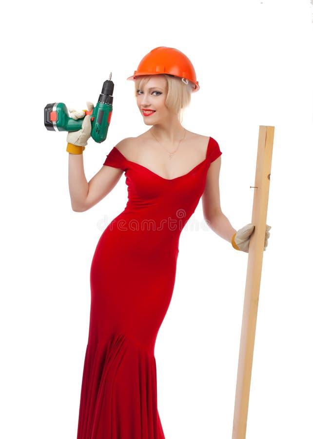 Belle blonde dans une robe rouge avec un foret électrique images libres de droits