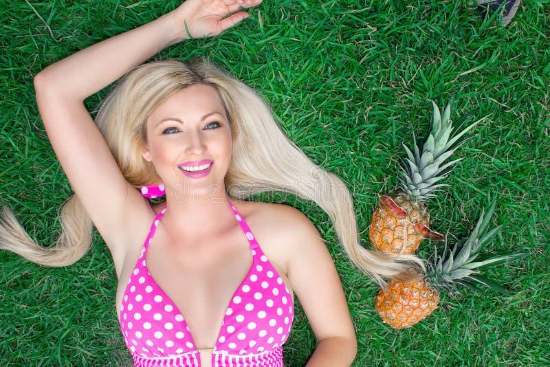 Belle blonde de jeune femme dans un bikini rose se trouvant sur l'herbe avec deux ananas photo stock