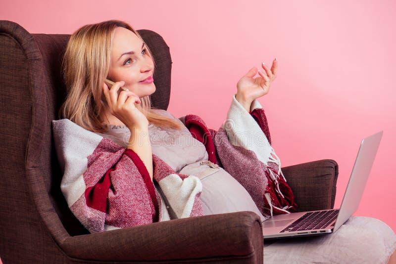 Belle blonde heureuse femme enceinte grande bosse assise dans une chaise confortable recouverte d'une couverture chaude et parlan photos libres de droits