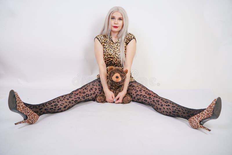 Belle blonde potelée de platine avec les lèvres rouges utilisant la robe courte d'impression de léopard et le collant noir sur images stock